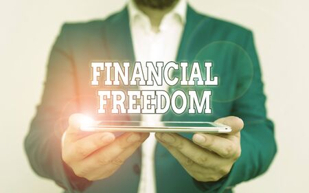 Text sign showing Financial Freedom. Business photo text make big life decisions without being stressed about money Businessman holds laptop in his hand. Man holding mobile phone with touch screen