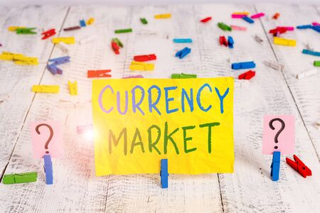 Conceptual hand writing showing Currency Market. Concept meaning over the counter market for the trading of currencies Crumbling sheet with paper clips placed on the wooden table Archivio Fotografico
