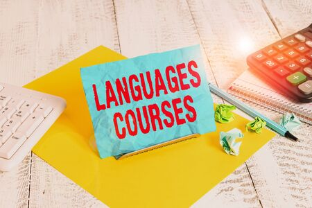 Text sign showing Languages Courses. Business photo text set of classes or a plan of study on a foreign language Notepaper stand on buffer wire in between computer keyboard and math sheets