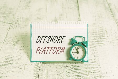 Word writing text Offshore Platform. Business photo showcasing structure with facilities for well drilling to explore Mini blue alarm clock stand tilted above buffer wire in front of notepaper Imagens