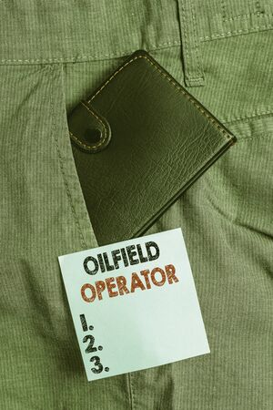 Handwriting text Oilfield Operator. Conceptual photo responsible for optimizing production of the oil wells Small little wallet inside man trousers front pocket near notation paper Foto de archivo - 139416500