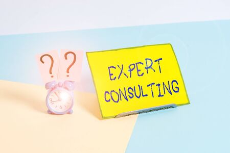Word writing text Expert Consulting. Business photo showcasing providing of expert knowledge to a third party for a fee Mini size alarm clock beside a Paper sheet placed tilted on pastel backdrop