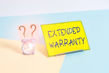 Word writing text Extended Warranty. Business photo showcasing contract which gives a prolonged warranty to consumers Mini size alarm clock beside a Paper sheet placed tilted on pastel backdrop