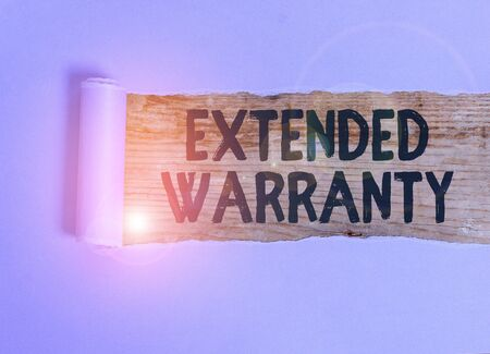 Handwriting text Extended Warranty. Conceptual photo contract which gives a prolonged warranty to consumers Cardboard which is torn in the middle placed above a wooden classic table