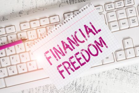 Writing note showing Financial Freedom. Business concept for make big life decisions without being stressed about money Keyboard office supplies rectangle shape paper reminder wood