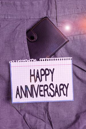 Word writing text Happy Anniversary. Business photo showcasing The annually recurring date of a past event celebration Small little wallet inside man trousers front pocket near notation paper