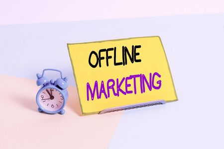 Text sign showing Offline Marketing. Business photo showcasing Advertising strategy published outside of the internet Mini size alarm clock beside a Paper sheet placed tilted on pastel backdrop 스톡 콘텐츠