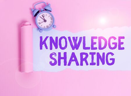 Writing note showing Knowledge Sharing. Business concept for deliberate exchange of information that helps with agility Alarm clock and torn cardboard placed above plain pastel table backdrop