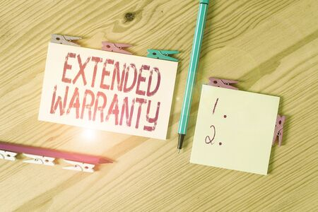 Handwriting text Extended Warranty. Conceptual photo contract which gives a prolonged warranty to consumers Colored clothespin papers empty reminder wooden floor background office Banco de Imagens - 139415345