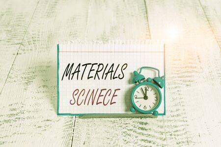 Word writing text Materials Science. Business photo showcasing interdisciplinary field involving the properties of matter Mini blue alarm clock stand tilted above buffer wire in front of notepaper Фото со стока
