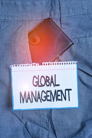 Word writing text Global Management. Business photo showcasing way an organization analysis its business internationally Small little wallet inside man trousers front pocket near notation paper