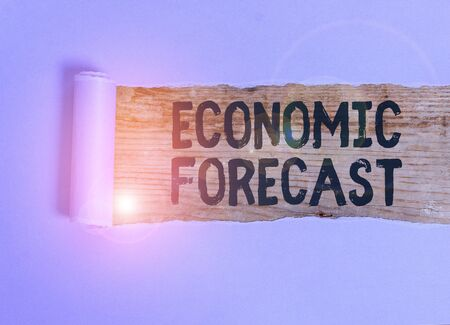 Handwriting text Economic Forecast. Conceptual photo attempting to predict the future condition of the economy Cardboard which is torn in the middle placed above a wooden classic table 스톡 콘텐츠