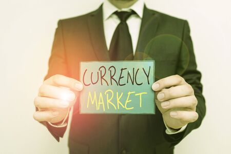 Conceptual hand writing showing Currency Market. Concept meaning over the counter market for the trading of currencies Male human wear formal work suit with office look hold book Archivio Fotografico