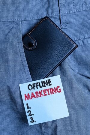 Handwriting text Offline Marketing. Conceptual photo Advertising strategy published outside of the internet Small little wallet inside man trousers front pocket near notation paper 스톡 콘텐츠