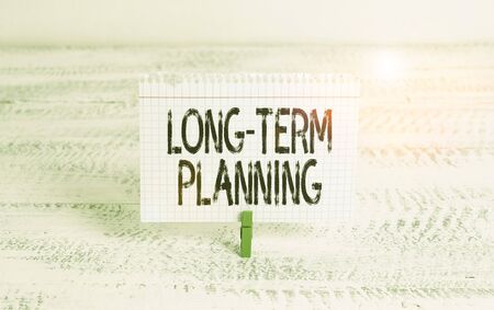 Writing note showing Long Term Planning. Business concept for establishing goals that you expected to achieve Green clothespin white wood background reminder office supply