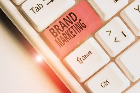 Writing note showing Brand Marketing. Business concept for creating a name that identifies and differentiates a product