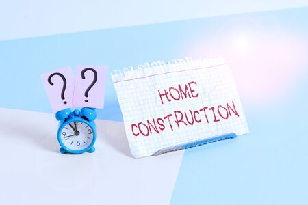 Text sign showing Home Construction. Business photo text the process of constructing a living accommodation Mini size alarm clock beside a Paper sheet placed tilted on pastel backdrop