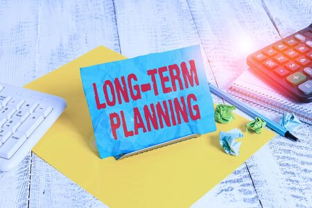 Text sign showing Long Term Planning. Business photo text establishing goals that you expected to achieve Notepaper stand on buffer wire in between computer keyboard and math sheets