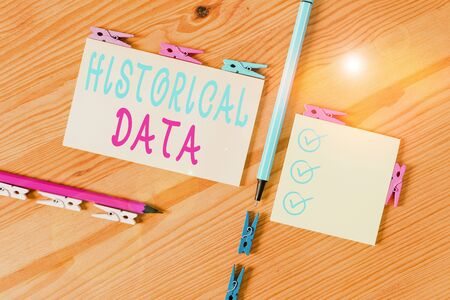 Text sign showing Historical Data. Business photo showcasing collected data about past events and circumstances Colored clothespin papers empty reminder wooden floor background office Archivio Fotografico