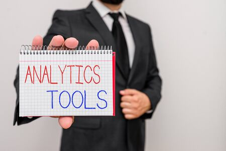Conceptual hand writing showing Analytics Tools. Concept meaning pieces of web application analysis software used to monitor Male human wear formal work suit with office look hold book