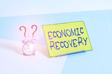 Word writing text Economic Recovery. Business photo showcasing rise of business activity signaling the end of a recession Mini size alarm clock beside a Paper sheet placed tilted on pastel backdrop
