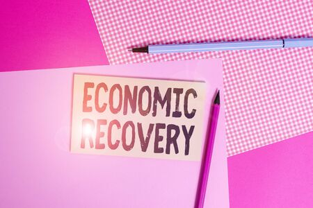 Conceptual hand writing showing Economic Recovery. Concept meaning rise of business activity signaling the end of a recession writing equipments and plain note paper placed on the table