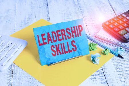 Text sign showing Leadership Skills. Business photo text Skills and qualities that leaders possess Taking a lead Notepaper stand on buffer wire in between computer keyboard and math sheets