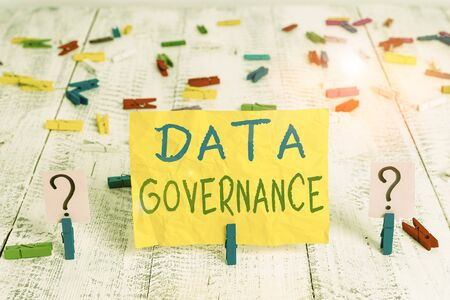 Conceptual hand writing showing Data Governance. Concept meaning general management of key data resources in a company Crumbling sheet with paper clips placed on the wooden table