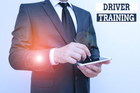 Conceptual hand writing showing Driver Training. Concept meaning course of study that teaches how to drive a vehicle Male human wear formal work suit hold smartphone using hand