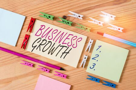 Word writing text Business Growth. Business photo showcasing process of improving some measure of an enterprise success Colored clothespin papers empty reminder wooden floor background office