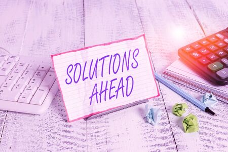 Conceptual hand writing showing Solutions Ahead. Concept meaning in advance action or process of solving a problem or issue Notepaper on wire in between computer keyboard and sheets