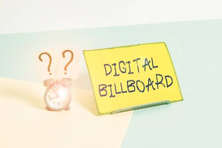 Word writing text Digital Billboard. Business photo showcasing billboard that displays digital images for advertising Mini size alarm clock beside a Paper sheet placed tilted on pastel backdrop