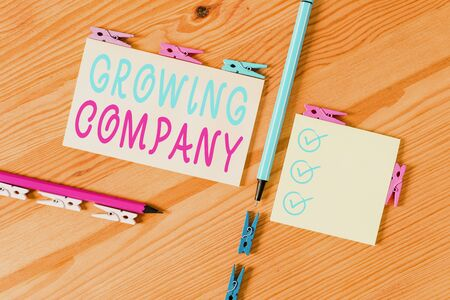 Text sign showing Growing Company. Business photo showcasing generates significant positive cash flows or earnings Colored clothespin papers empty reminder wooden floor background office Banco de Imagens