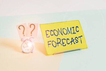 Word writing text Economic Forecast. Business photo showcasing attempting to predict the future condition of the economy Mini size alarm clock beside a Paper sheet placed tilted on pastel backdrop 스톡 콘텐츠