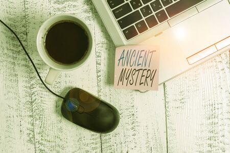 Writing note showing Ancient Mystery. Business concept for anything that is kept secret or remains unexplained Trendy metallic laptop blank sticky note coffee cup mouse lying vintage Stock Photo