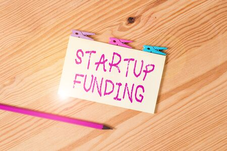 Text sign showing Startup Funding. Business photo text financial investment in the development of a new company Colored clothespin papers empty reminder wooden floor background office