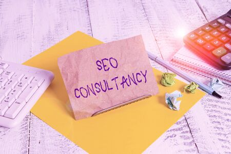 Writing note showing Seo Consultancy. Business concept for specialize in evaluating an organization website Notepaper on wire in between computer keyboard and sheets