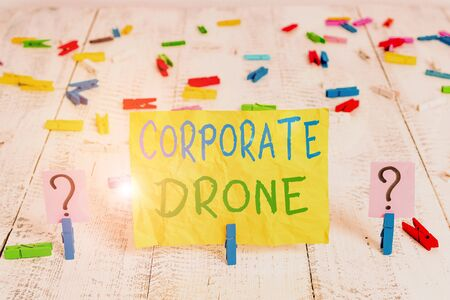 Conceptual hand writing showing Corporate Drone. Concept meaning unmanned aerial vehicles used to monitor business vicinity Crumbling sheet with paper clips placed on the wooden table