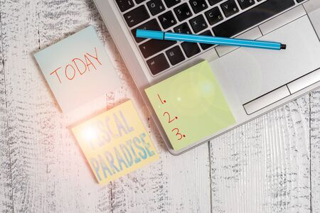 Writing note showing Fiscal Paradise. Business concept for Tax on development Rates of taxation for foreign investors Trendy metallic laptop three sticky note pads pen on vintage table desk