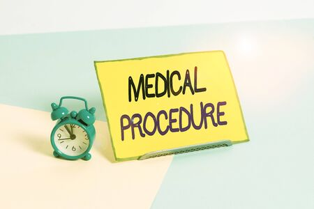 Text sign showing Medical Procedure. Business photo showcasing a procedure employed by medical or dental practitioners Mini size alarm clock beside a Paper sheet placed tilted on pastel backdrop