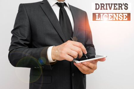 Conceptual hand writing showing Driver S License. Concept meaning a document permitting a demonstrating to drive a motor vehicle Male human wear formal work suit hold smartphone using hand