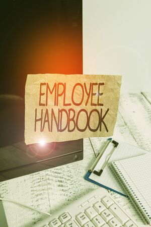 Conceptual hand writing showing Employee Handbook. Concept meaning states the rules and regulations and policies of a company Note paper taped to black screen near keyboard stationary Stock Photo