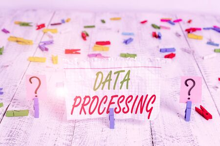 Writing note showing Data Processing. Business concept for collection and manipulation of items of data to produce Crumbling sheet with paper clips placed on the wooden table