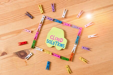 Text sign showing Cloud Solutions. Business photo text ondemand services or resources accessed via the internet Colored clothespin papers empty reminder wooden floor background office