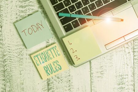 Writing note showing Etiquette Rules. Business concept for customs that control accepted behaviour in social groups Trendy metallic laptop three sticky note pads pen on vintage table desk