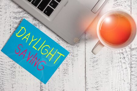 Conceptual hand writing showing Daylight Saving. Concept meaning turning the clock ahead as warmer weather approaches Metallic laptop blank sticky note coffee cup lying vintage table