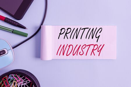Conceptual hand writing showing Printing Industry. Concept meaning industry involved in production of printed matter Notebook and stationary with gadgets above pastel backdrop