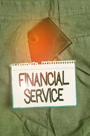 Word writing text Financial Service. Business photo showcasing economic services provided by the finance industry Small little wallet inside man trousers front pocket near notation paper