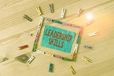 Conceptual hand writing showing Leadership Skills. Concept meaning Skills and qualities that leaders possess Taking a lead Colored crumpled papers wooden floor background clothespin