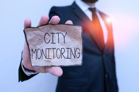 Text sign showing City Monitoring. Business photo text indicator level analysis pilot project on urban food systems Male human wear formal work suit office look hold notepaper sheet use hand